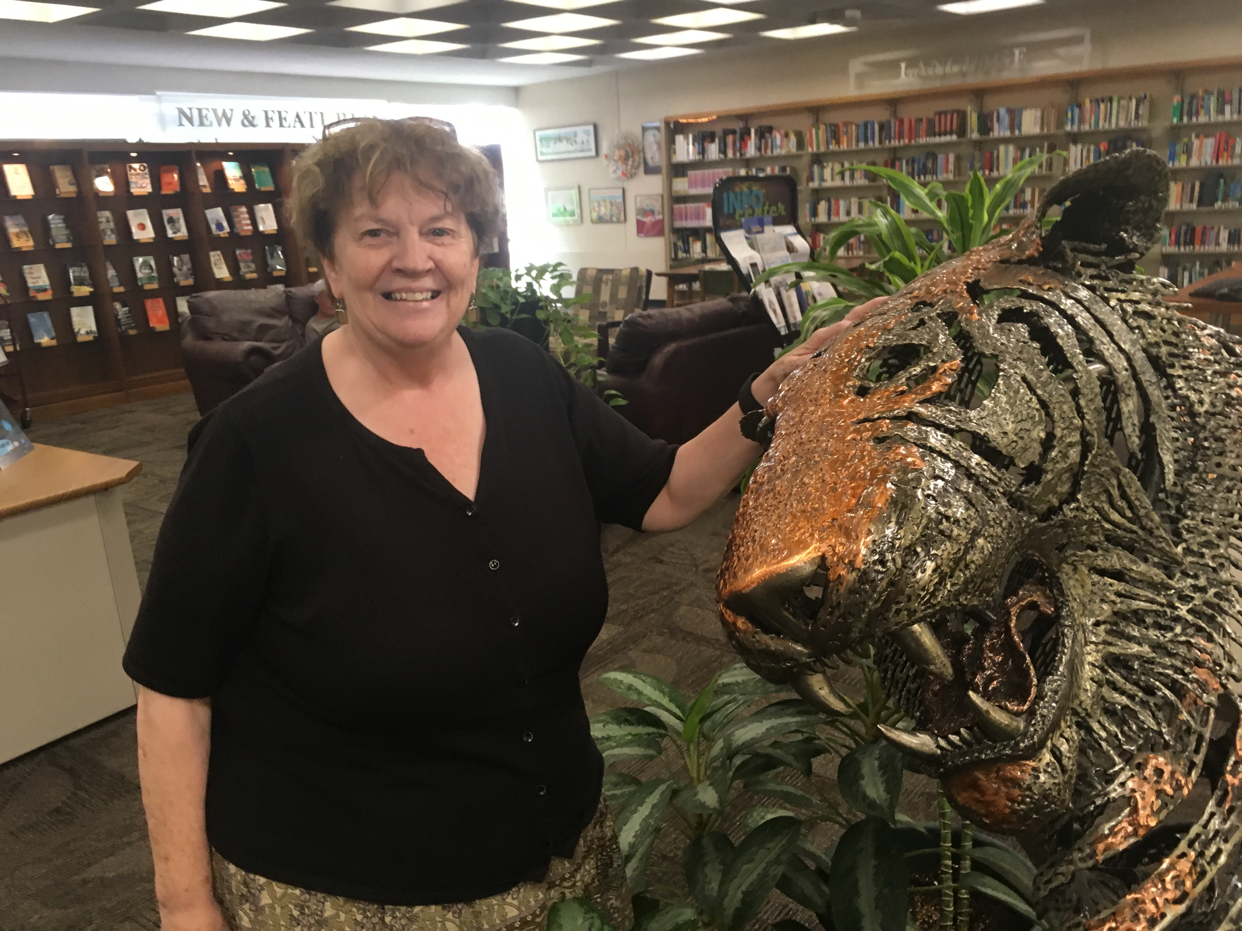 Janet McKenney with tiger sculpture at the Maine State Library