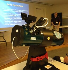 Library telescope with astronomy presentation in background